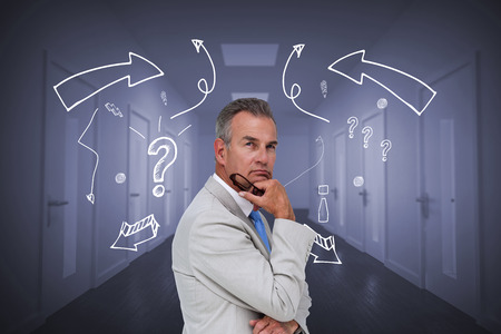 Thinking businessman against bright hallway with several doors Stock Photo