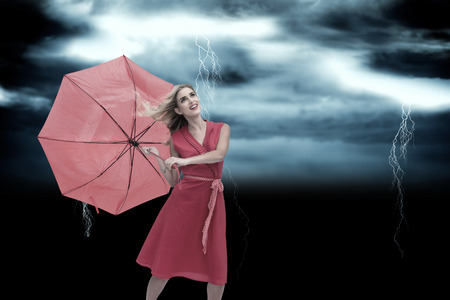 Elegant blonde holding umbrella against stormy dark sky with lightning bolts photo