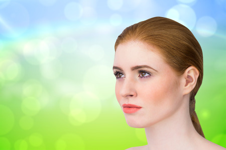 hair tied: Beautiful redhead posing with hair tied against green and blue abstract design