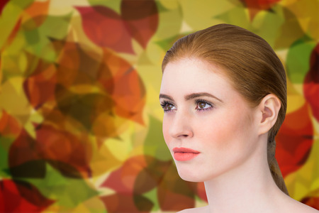 hair tied: Beautiful redhead posing with hair tied against autumnal leaf pattern in warm tones Stock Photo