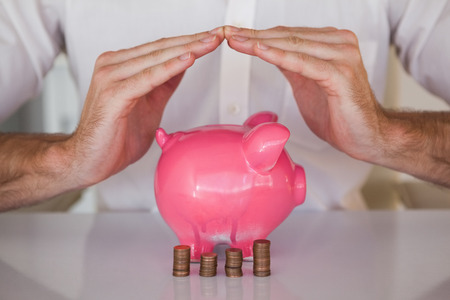 sheltering: Casual businessman sheltering piggy bank and coins in his office