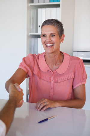 Laughing businesswoman shaking hands at desk in her office photo