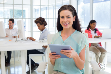 Businesswoman on tablet pc smiling at camera in the office photo