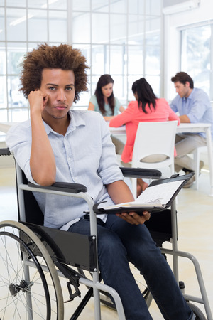 frowns: Stern businessman in wheelchair holds planner and frowns at camera in the office