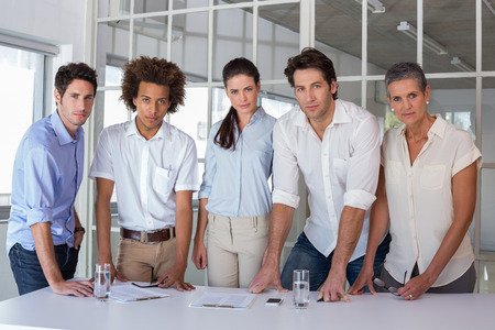 Casual business team having a meeting looking at camera in the office photo