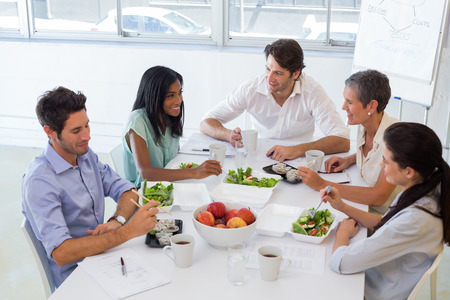 Business people eating lunch together in the office photo