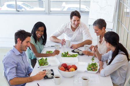 comer sano: Trabajadores charlando al mismo tiempo disfrutar de un almuerzo saludable en la oficina