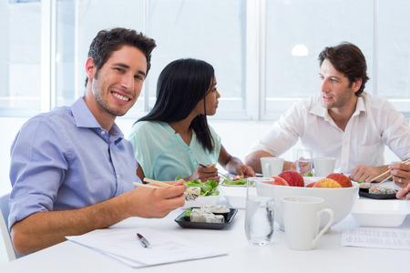 lunch meeting: Workers chat and smile to camera while enjoying lunch in the office Stock Photo