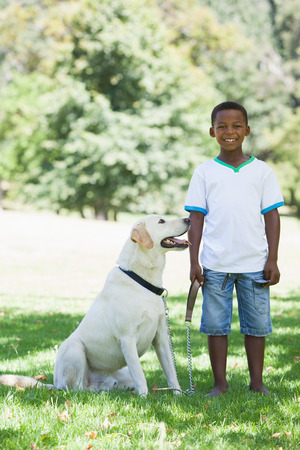 Little boy standing with his pet labrador in the park on a sunny day photo