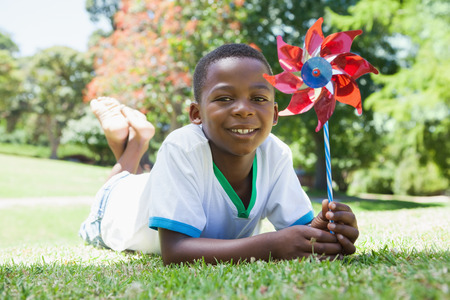 Little boy holding pinwheel in the park smiling at camera on a sunny day photo