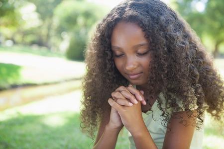 niño orando: Niña rezando en el parque en un día soleado