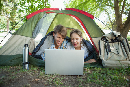 Cute couple lying in their tent using laptop on a sunny day photo