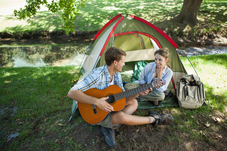 serenading: Cute man serenading his girlfriend on camping trip on a sunny day Stock Photo