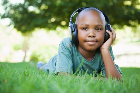 Little boy lying on grass listening to music and smiling on a sunny day photo