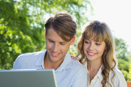 Cute couple sitting on park bench together looking at laptop on a sunny day photo