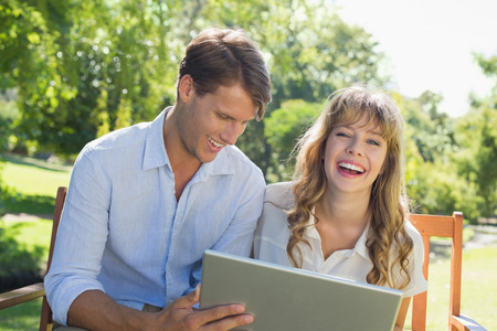 Cute couple sitting on park bench together using laptop and laughing on a sunny day photo