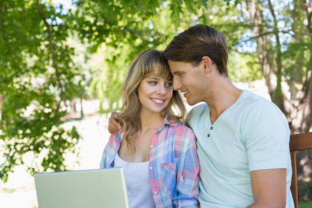 Smiling young couple sitting on park bench using laptop on a sunny day photo