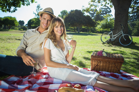 Cute couple drinking white wine on a picnic smiling at camera on a sunny day photo