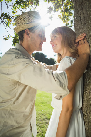 Cute couple leaning against tree in the park on a sunny day photo