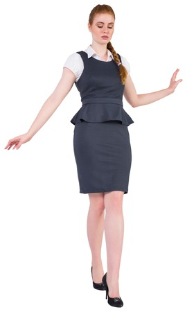 Businesswoman doing a balancing act on white background photo