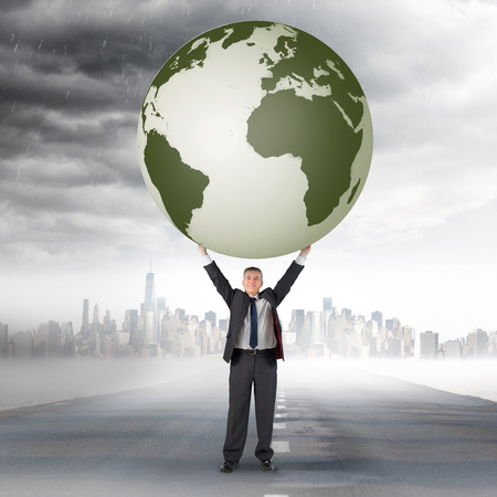 Composite image of businessman holding earth against open road photo