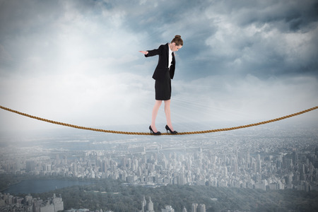 Businesswoman performing a balancing act against cityscape on a wall