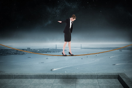 balancing act: Businesswoman performing a balancing act against balcony overlooking coastline at night Stock Photo
