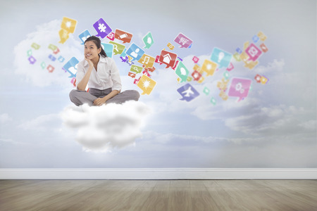 Businesswoman sitting cross legged thinking against clouds in a room photo