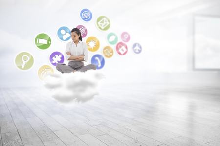 woman looking down: Grumpy businesswoman sitting cross legged against room with holographic cloud Stock Photo