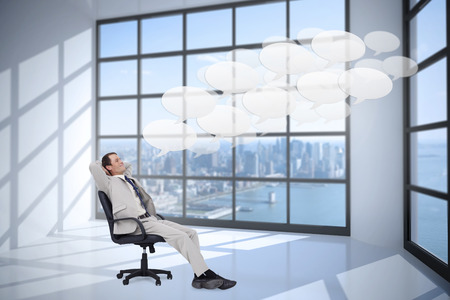 Side view of businessman leaning back in his chair against room with large window showing city photo