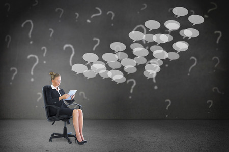 Businesswoman sitting on swivel chair with tablet against speech bubbles photo