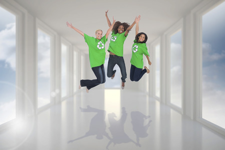 activists: Enviromental activists jumping and smiling against bright white hall with windows Stock Photo