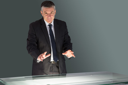Concentrating businessman looking at desk on black background photo