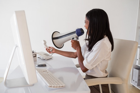 Angry businesswoman shouting in megaphone at phone in her office photo