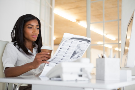 Pretty businesswoman reading newspaper at her desk in her office photo