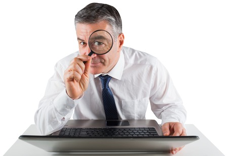 Mature businessman examining with magnifying glass on white background photo