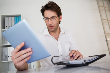 organizing: Casual businessman organizing his schedule at his desk in his office Stock Photo