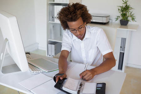 organizing: Casual young businessman organizing his schedule at his desk in his office Stock Photo