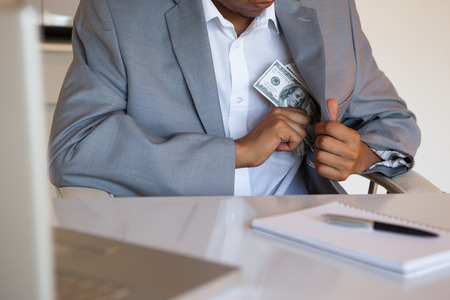 dodgy: Dodgy businessman pocketing wad of dollars in his office