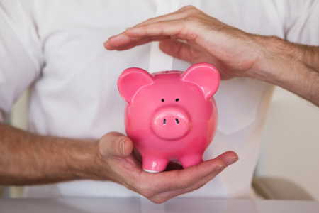 cradling: Casual businessman holding piggy bank in his office Stock Photo