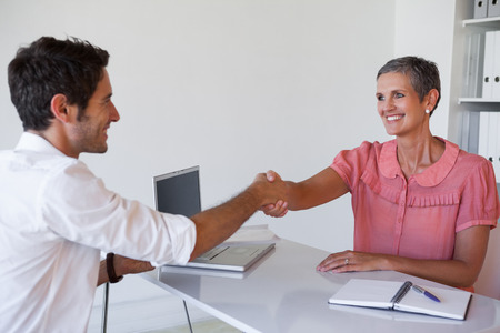Casual business people shaking hands at desk in the office photo