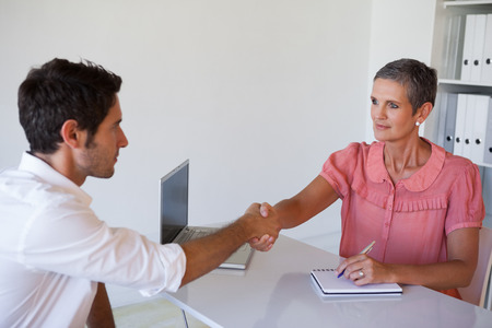 Casual business people shaking hands at desk in her office photo