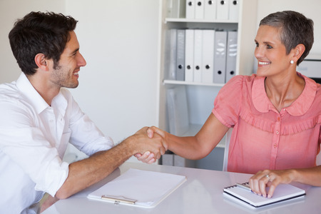 Casual business people shaking hands at desk and smiling in her office photo
