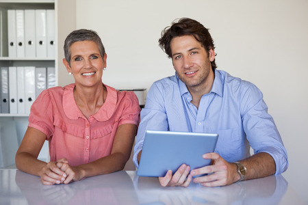 Casual smiling business team working at desk using tablet in the office photo
