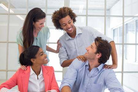 congratulating: Workers congratulating and praising one another in the office