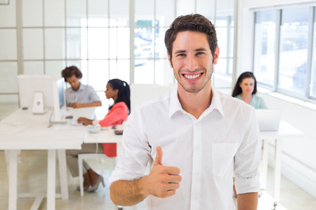 Smiling worker giving thumbs up in the office photo