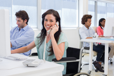 Attractive businesswoman in wheelchair on phone in the office Stock Photo