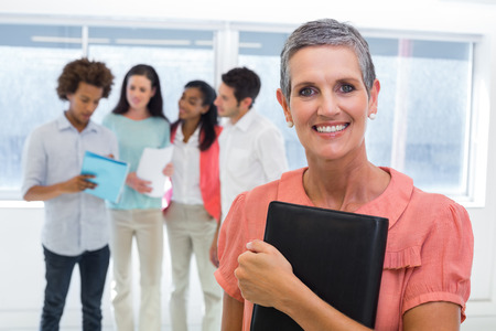 Businesswoman holds planner and smiles at camera while colleagues stand behind in the office photo