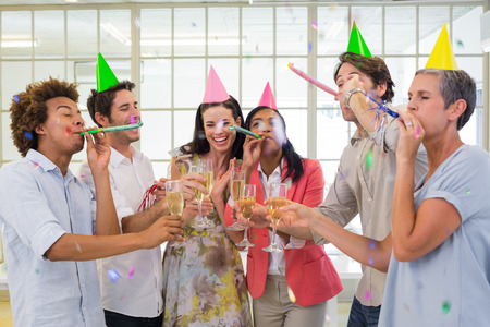 party poppers: Casual business team celebrating with champagne and party horns in the office Stock Photo