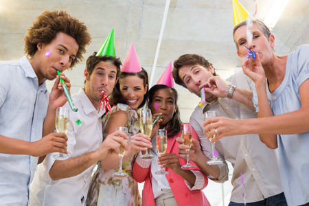Business people celebrating at the workplace with glasses of champagne while smiling at the camera photo